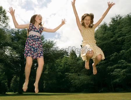 girls jumping in garden