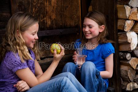two girls eating fruit drinking