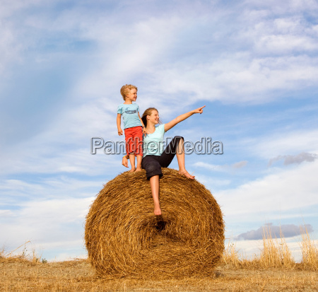 girl and boy standing on hay