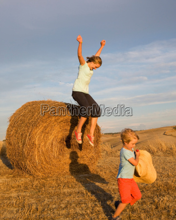 girl and boy with hay bale