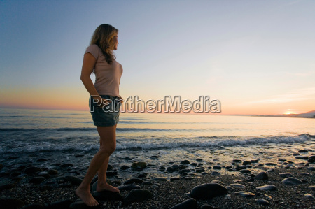 woman on beach watching sunset low
