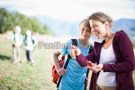woman watching a compass with boy