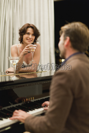 man playing piano for girlfriend at