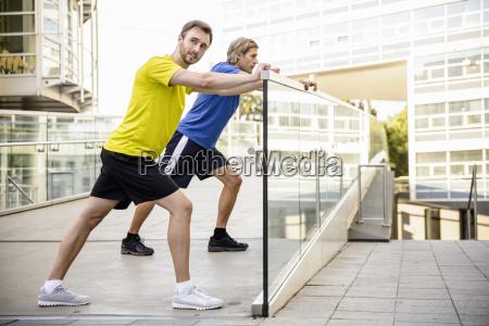 due uomini appoggiati e allungati gambe