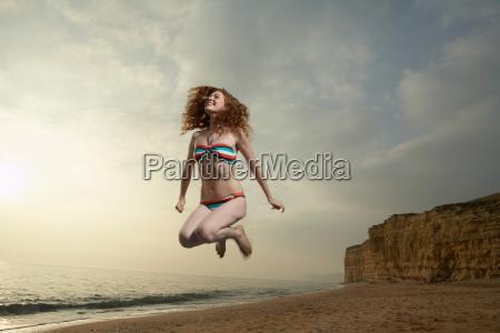 donna, che, salta, con, sfondo, spiaggia - 18222886