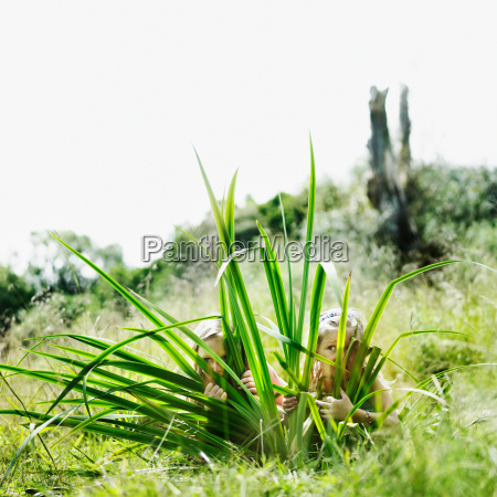 girls hiding behind palm plant