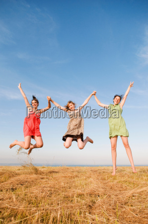 three girls jump and hold hands