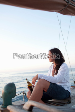 woman drinking beer watching sunset