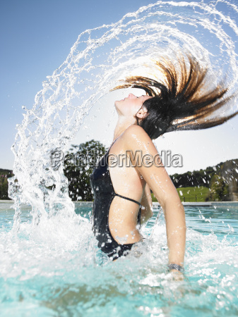 young woman jumping out of water