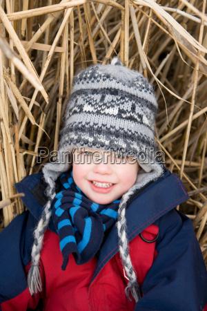 boy sitting in straw