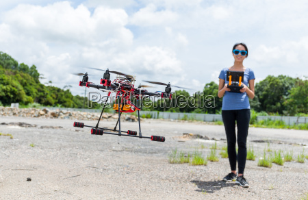 woman control the flying drone at