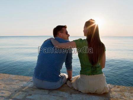 couple by sea watching sun set