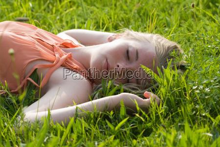 teenage girl laying in tall grass
