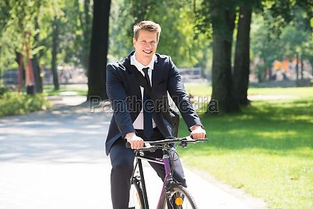 uomo daffari in bicicletta nel parco