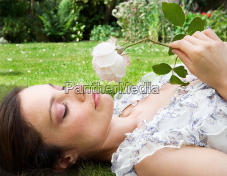 woman laying on grass smelling a