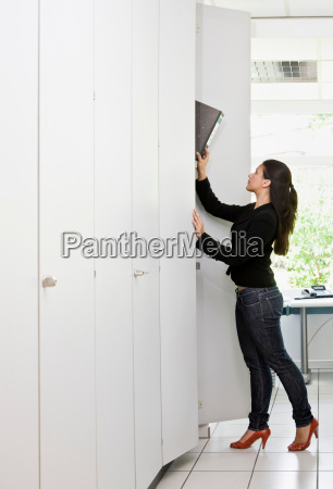woman looking through files in office