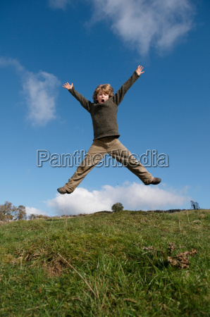 boy jumping on hill