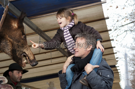 girl touching boars head at market