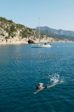 woman swimming with boat in background