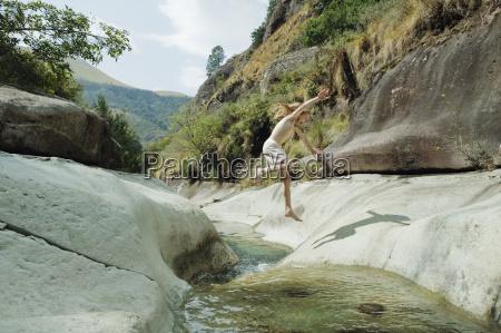 girl jumping over stream