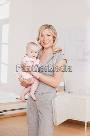 young businesswoman holding a baby