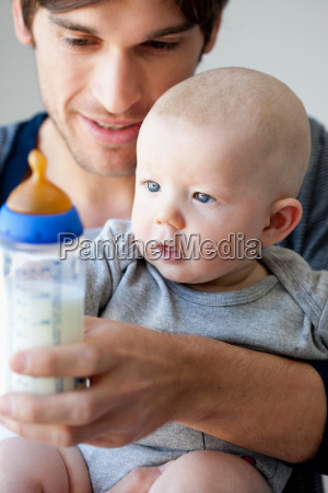 father offering baby bottle
