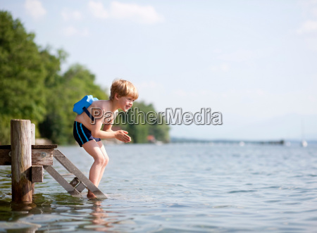 boy jumping in water with swimming