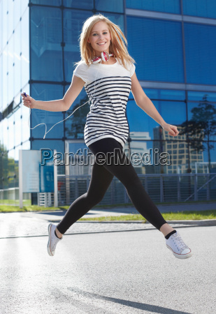 women jumping with mp3 player