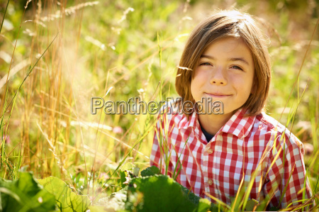 boy sitting in tall grass
