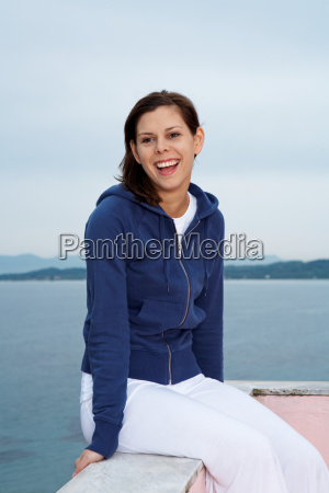 smiling young woman sitting on balcony