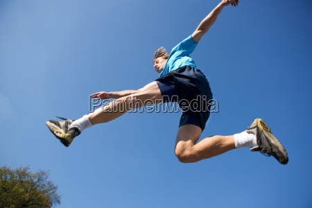 young man jumping in sports kit