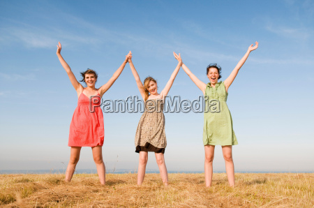 three teenage girls hold hands up