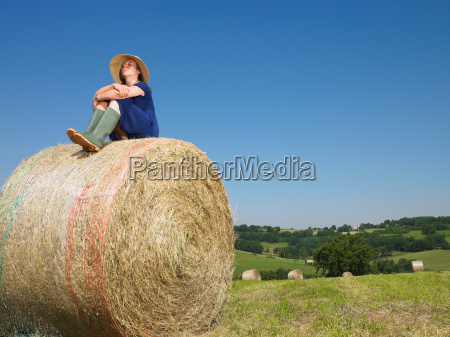 girl sitting on top of bale