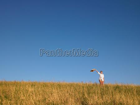 woman waving hat in field