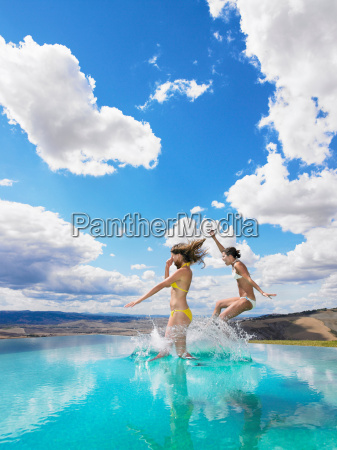 women jumping in swimming pool