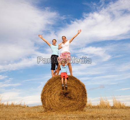 girl woman boy standing on hay