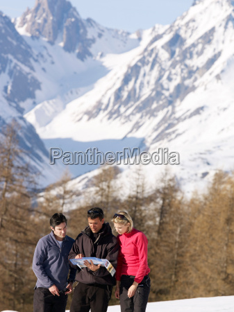 three people looking at map on