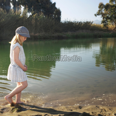 young girl by river with feet