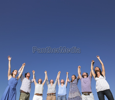 group of young people raising arms