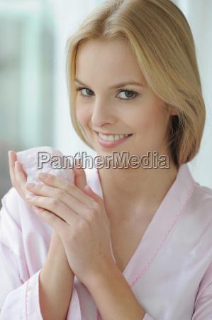 smiling woman holding rose quartz