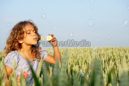 girl blowing bubbles in a wheat
