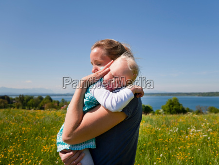 woman holding daughter in field