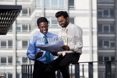 two businessmen looking at paper lans