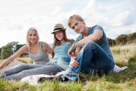three young persons sitting in grass