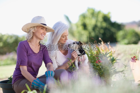 older women examining garden together