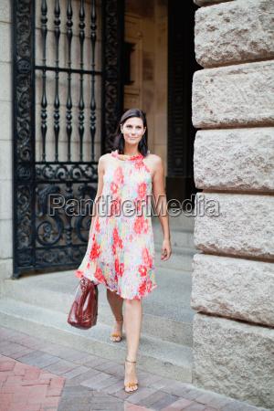 donna sorridente a piedi sulla strada