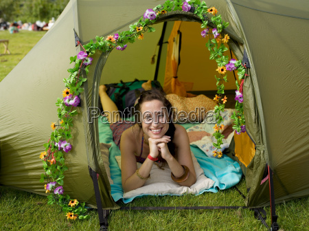 woman lying inside tent looking out
