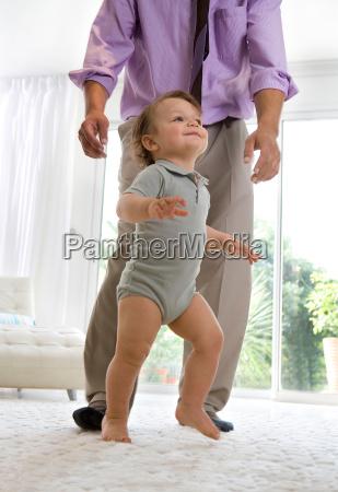 father watching baby walking