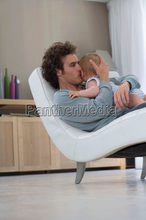 father kisses baby sits in chair