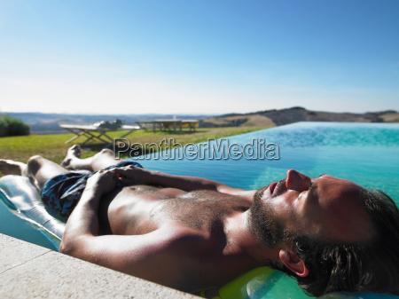 man resting in swimming pool